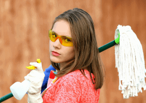 Young woman holding house cleaning tools before home appraisal
