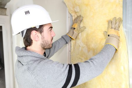 Man installing wall insulation to improve on the green-energy